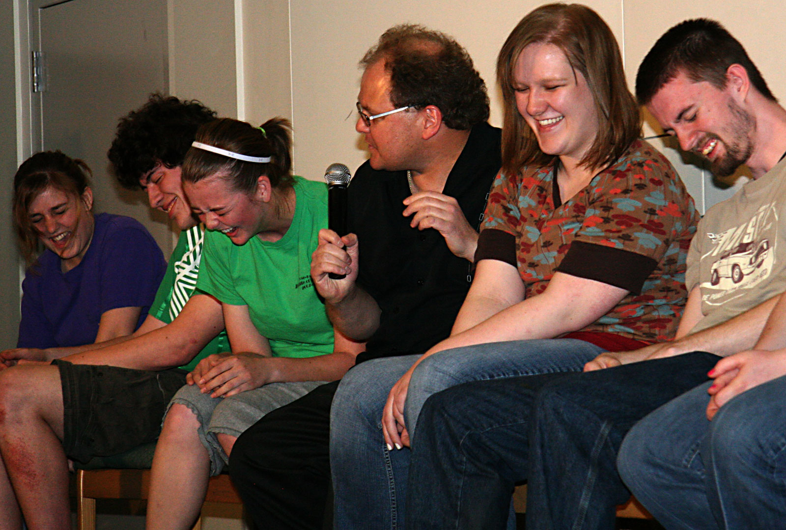 hypnotist chris cady with hypnotized college students laughing on stage in hypnotism show